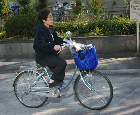 Another old lady riding in the Kyobashi train-station area in Osaka, Japan