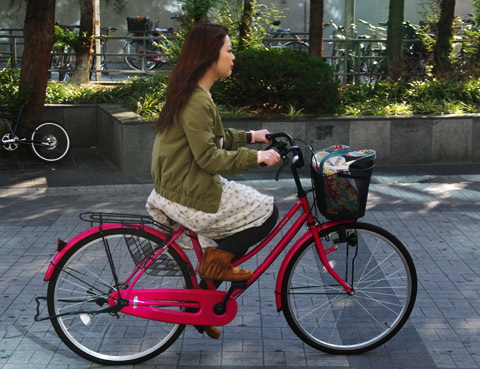 Young lady riding in the Kyobashi train-station area in Osaka, Japan