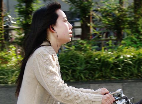 Listening to music, singing along the way, looks like she is really enjoying the ride. Osaka, Japan.