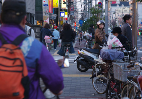 Lots of cyclist, old and young cycling on the pavement and peacefully mix with pedestrians in Osaka, Japan