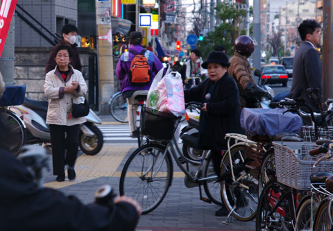 An old lady, Oba-san looking at me while prepare to ride her bike on the pavement in Osaka, Japan