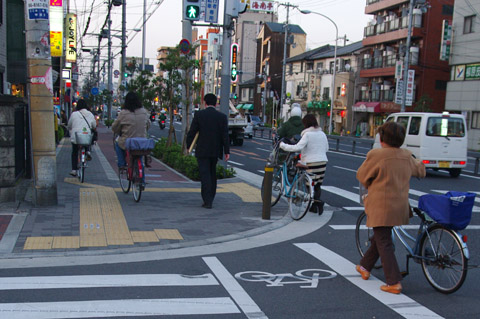 The bicycle sign on the crossing clearly indicate this is a share crossing for cyclist and pedestrians. Notice there is no kerb to hop when moving from road to pavement. Osaka, Japan