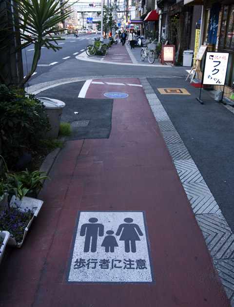 A sign on the cycling segment of a foot path- to remind cyclist of the pedestrian.  Notice there is no kerb to hop when moving from road to pavement. Osaka, Japan