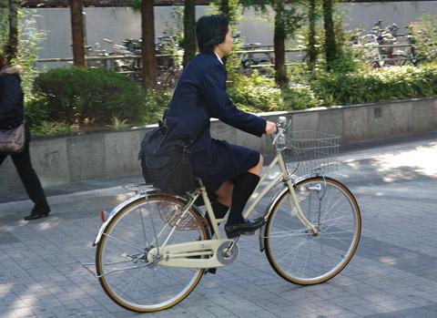 A smart lady riding towards the Kyobashi train-station in Osaka, Japan